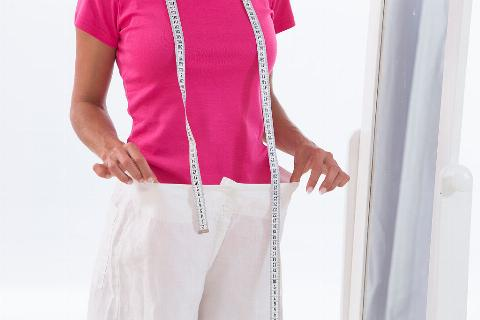 A woman holds up pants that are much too large for her, while holding a tape measure around her neck.