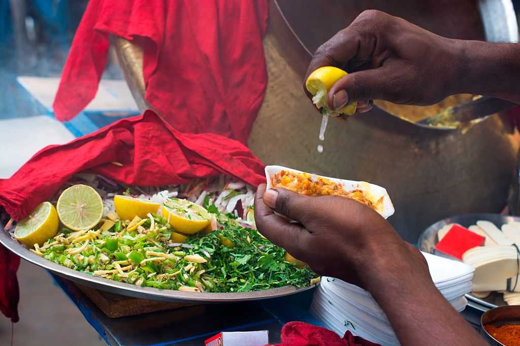 A person squeezes lemon over fried fish.