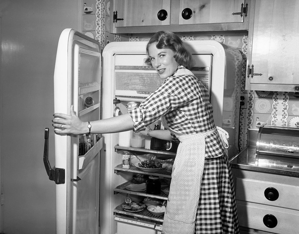 A 1950s woman reaches into the fridge while looking back at the camera