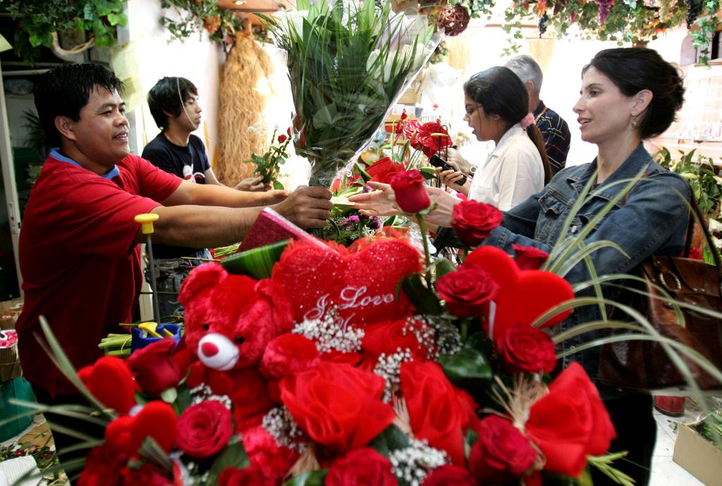A male florist sells a bouquet of flowers and Valentine's Day items