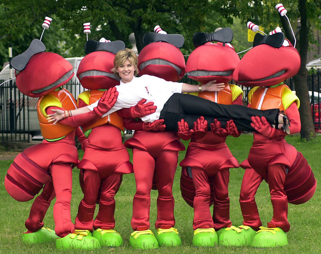 A woman is held up horizontally by people in ant outfits.