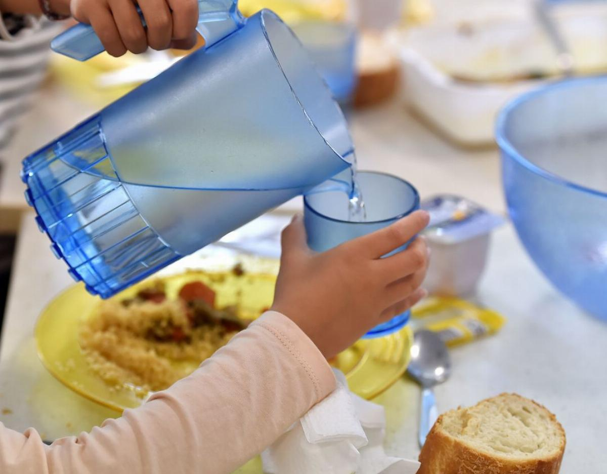 children pouring drinking water from a jug into a plastic beaker while eating lunch