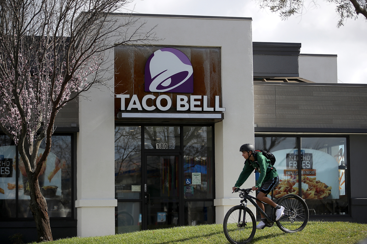 A customer rides his bike in front of a Taco Bell restaurant