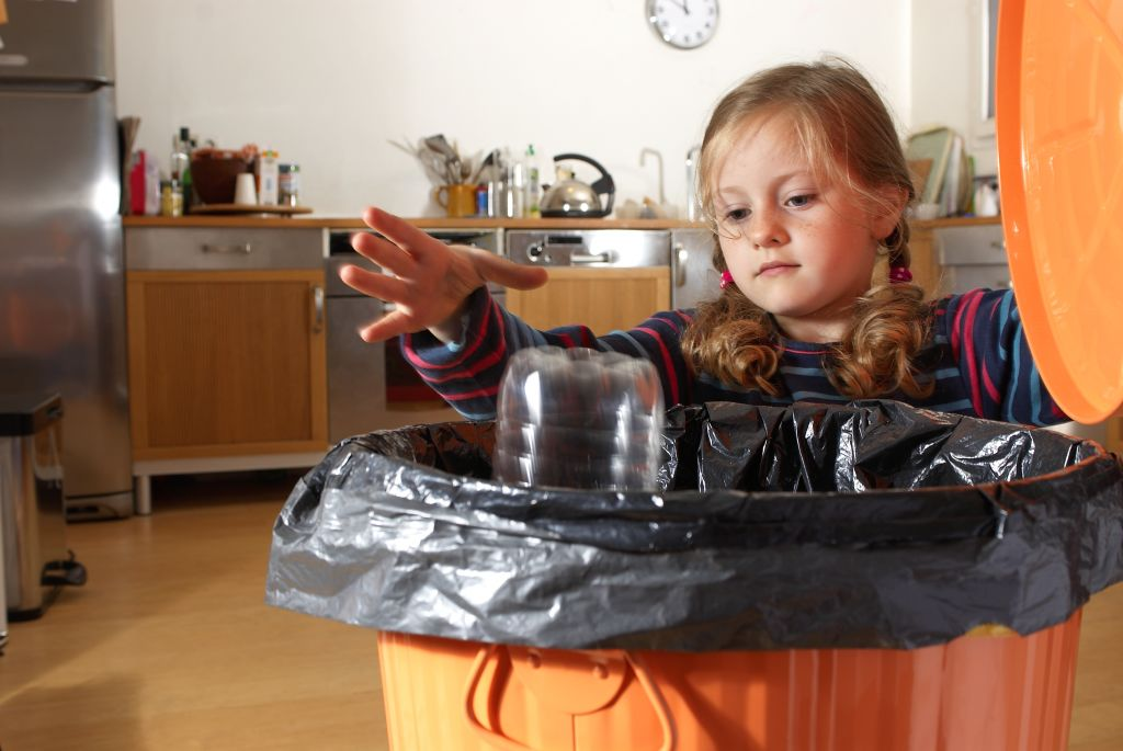 A young girl pulls off the lid of her garbage can to throw something away.