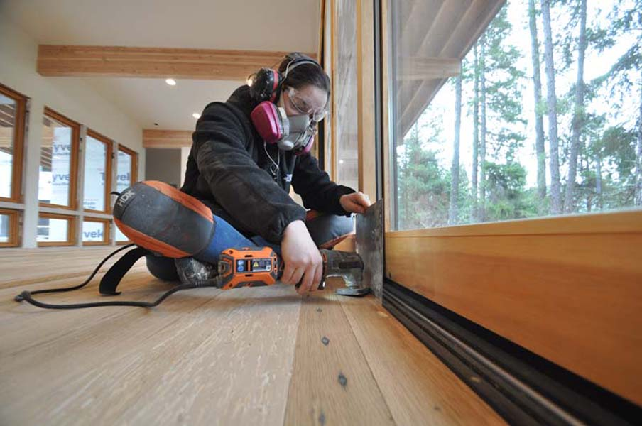 Amanda works on the hardwood floor in her new home
