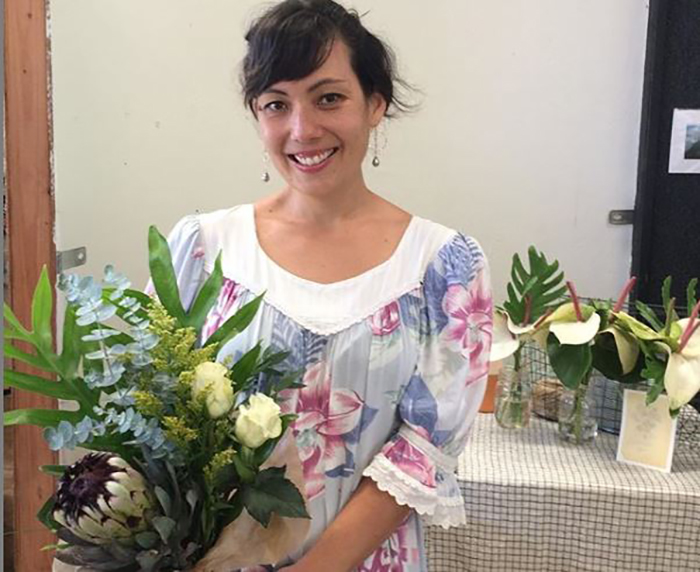 Shannon Hiramoto wears one of her muumuus while holding a bouquet