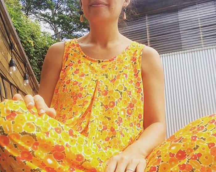 Shannon sits in a yellow floral muumuu