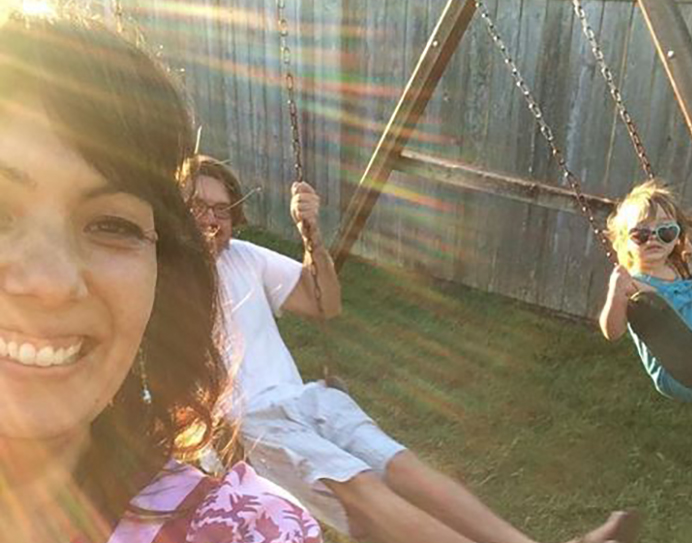 Shannon Hiramoto with her husband and daughter on their backyard swings