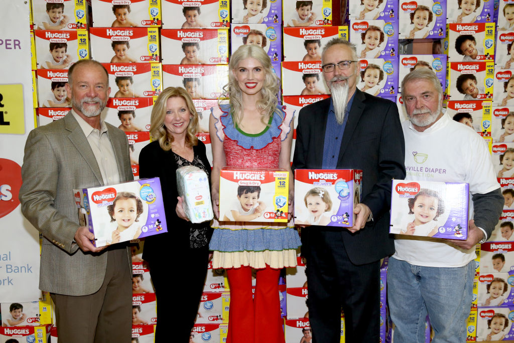 five people holding a box of diapers and standing in front of stacks of diapers