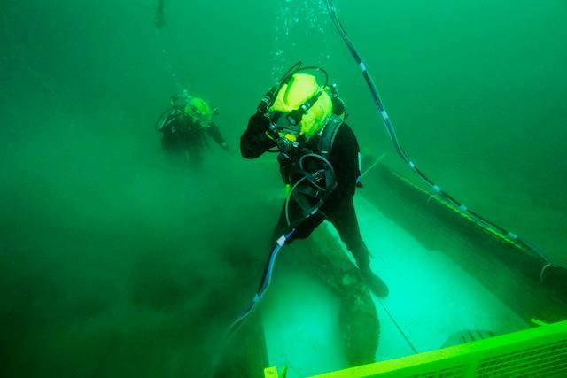 Divers are pictured underwater, securing the prototype to a pulley.
