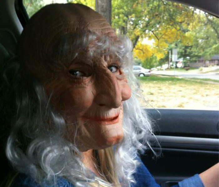 woman driving while wearing an old lady mask