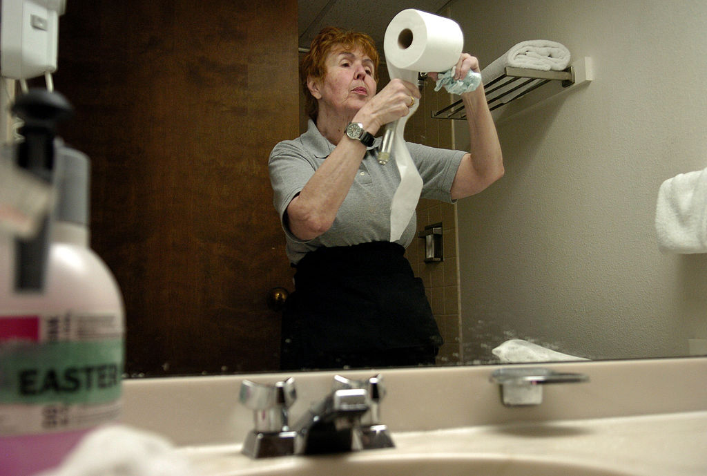 a woman putting toilet paper on a holder in a bathroom