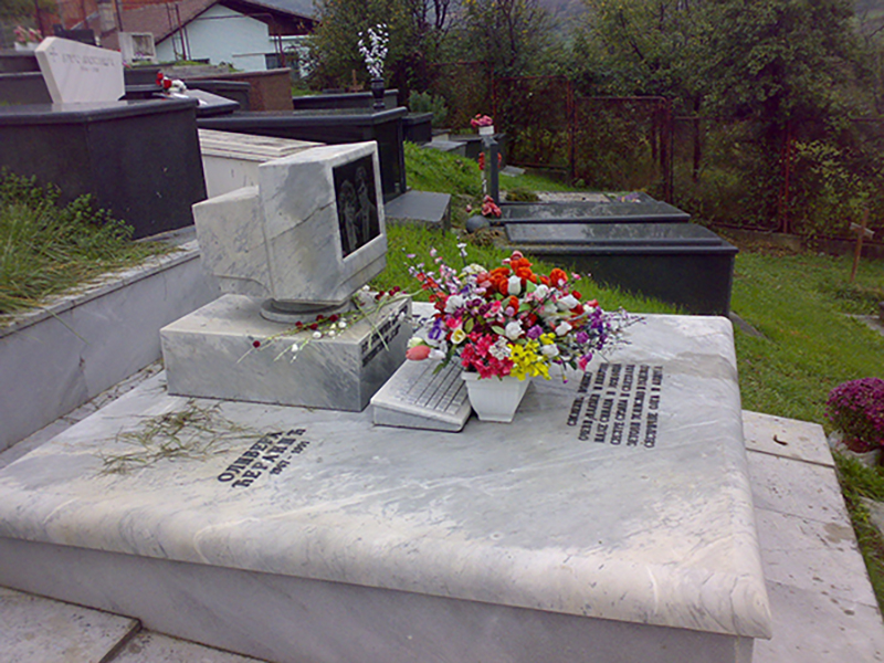 A replica of a 1990s computer serves as a headstone