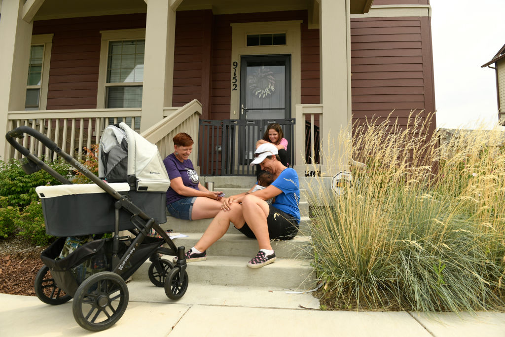Women gather on front porch steps to admire a baby