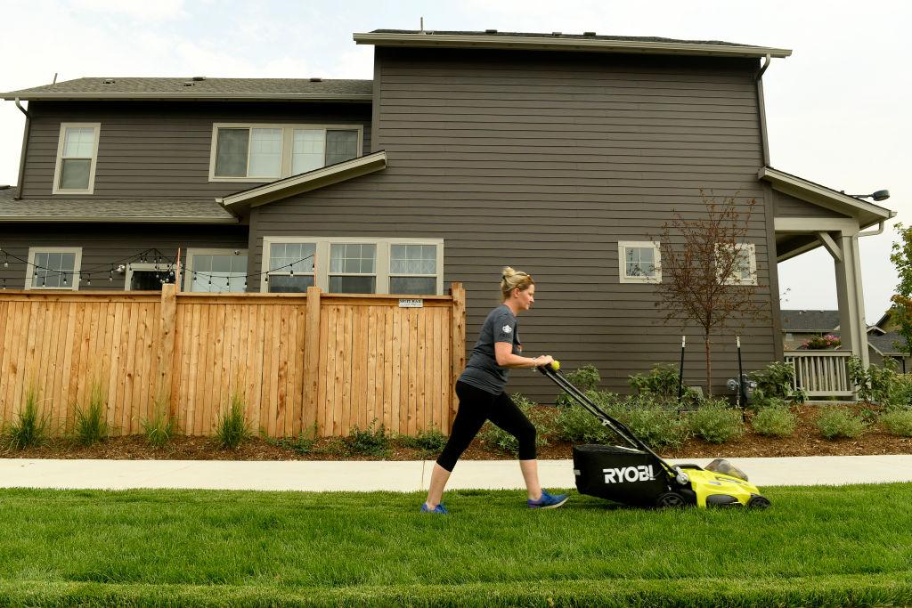 A woman mows her lawn