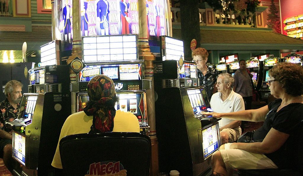 Patrons play slot machines in a casino
