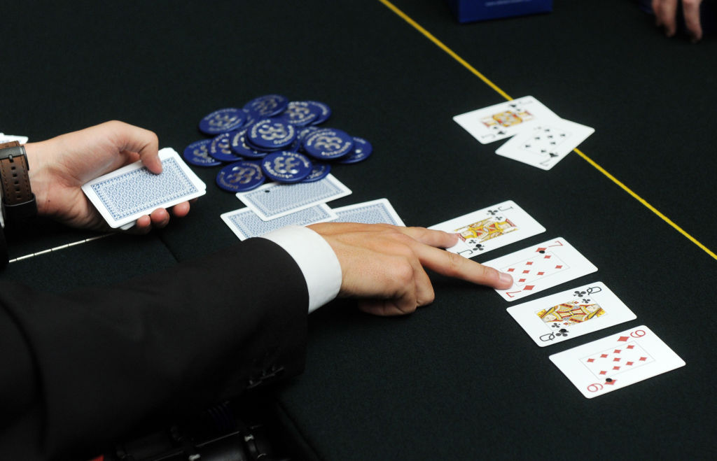 A dealer points to two of the cards he's dealt in poker