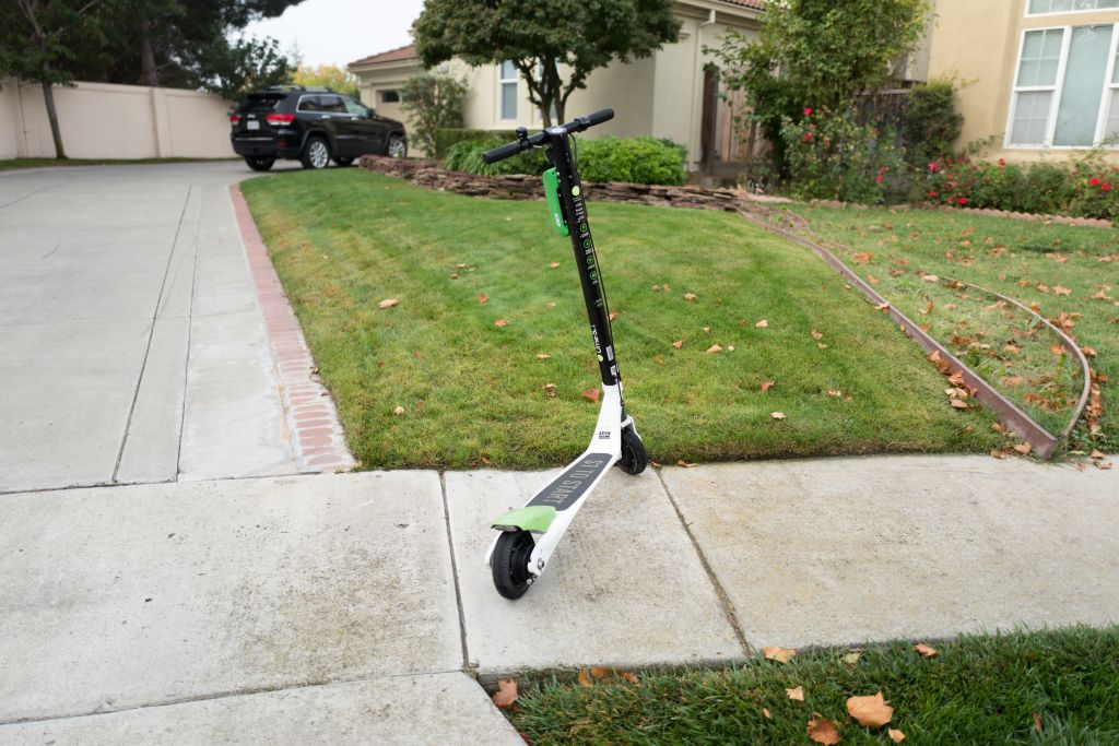 A scooter is left out on a sidewalk