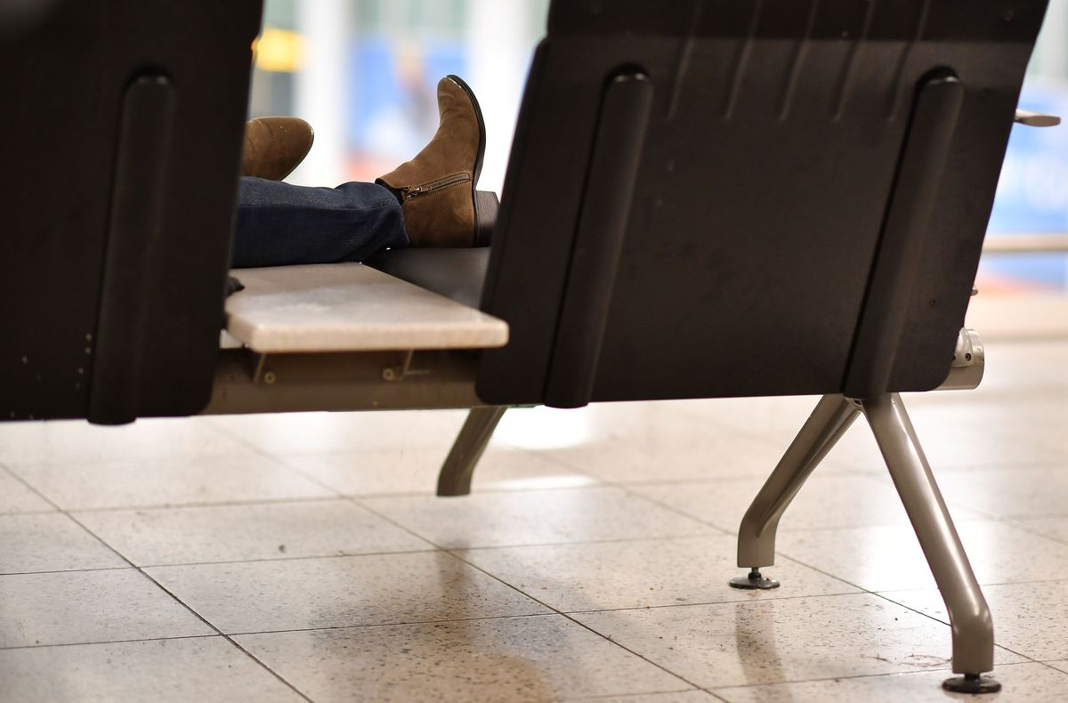 A passenger lays across chairs in the South Terminal building at London Gatwick Airport
