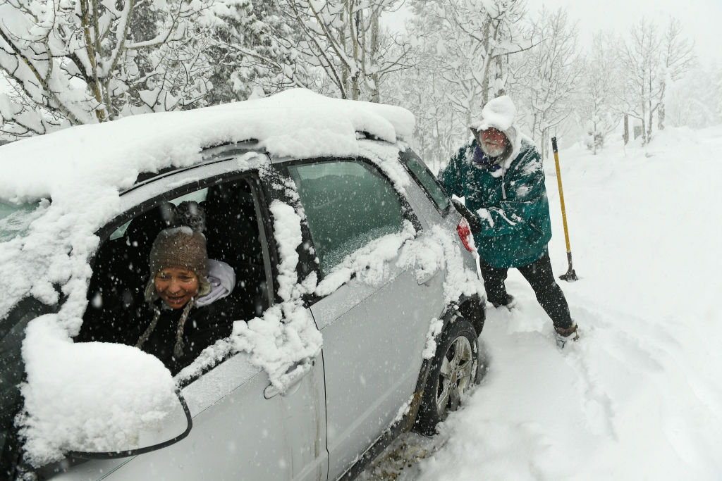 A man assists a woman while she's stuck in her car in a snowstorm