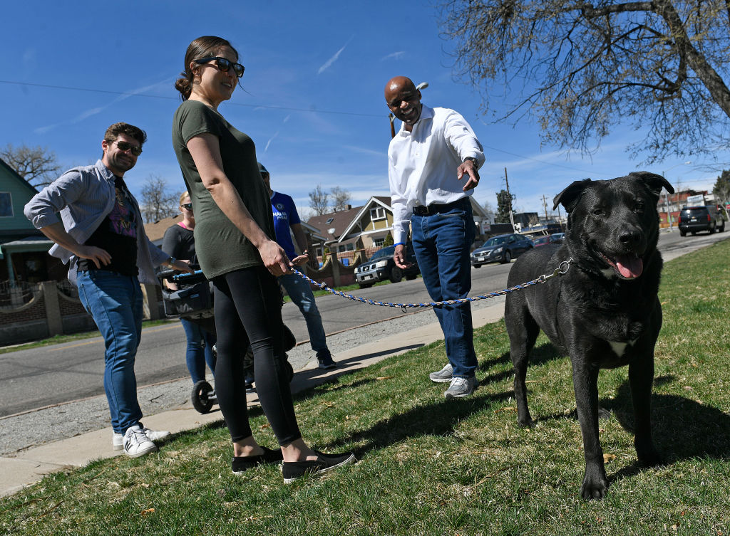 Neighbors admire a black, leashed dog