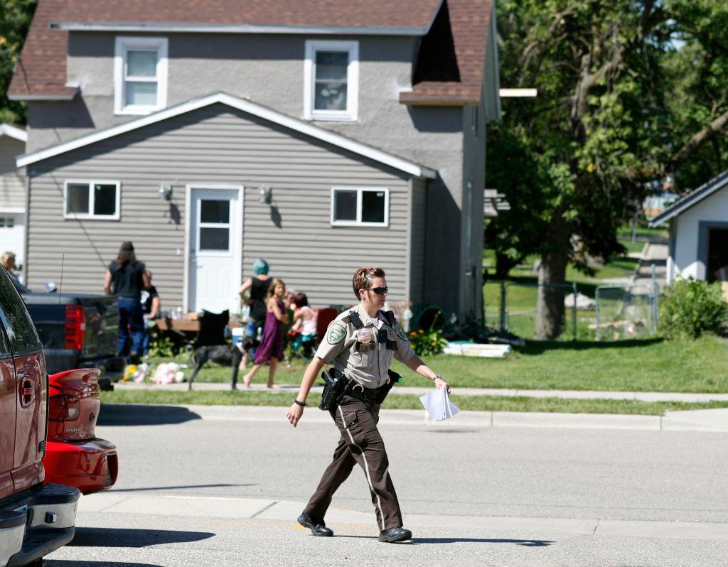 An officer struts down a neighborhood street