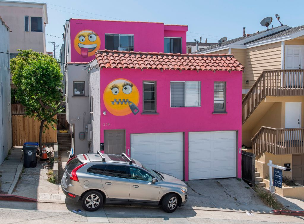 A hot pink house with emogis painted on