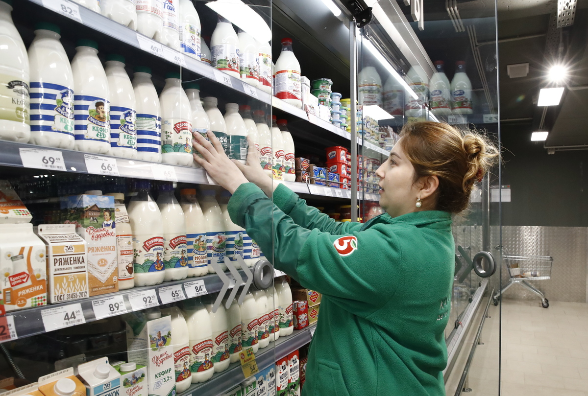 An employee arranges bottles of milk at a Pyaterochka grocery store.