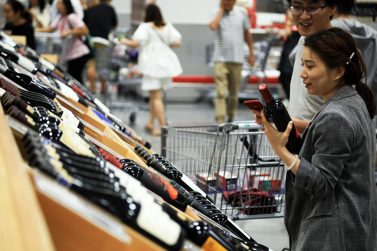 Customers look at bottles of red wine at Costco's first outlet in China
