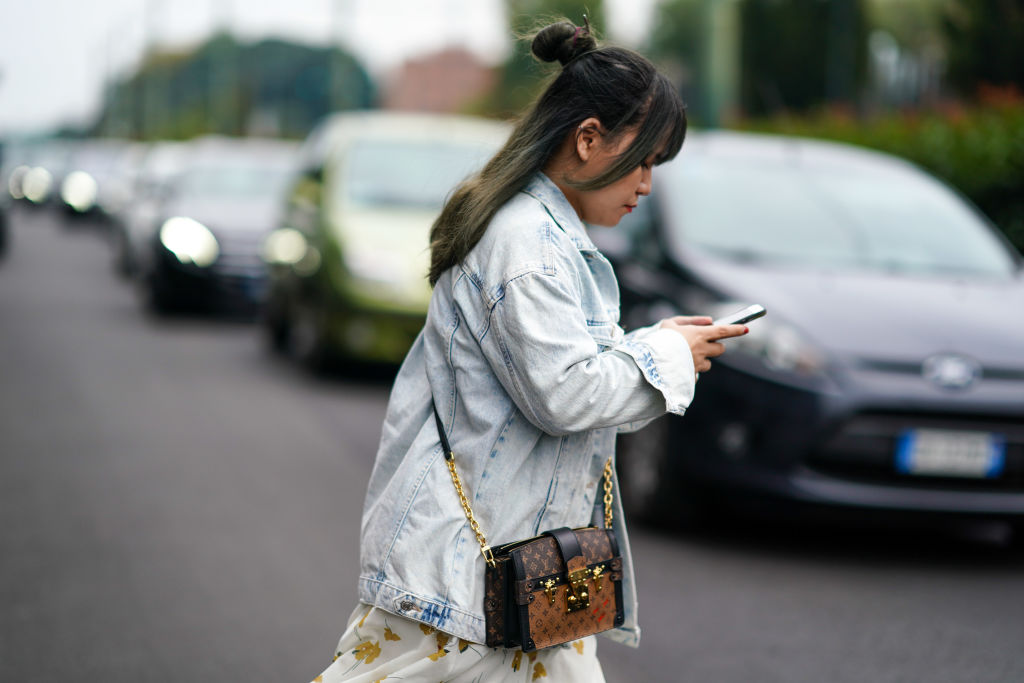 A woman texts while crossing the street