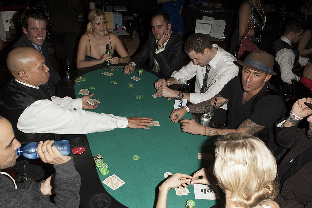 Players dressed in roaring 20s attire play a game of poker