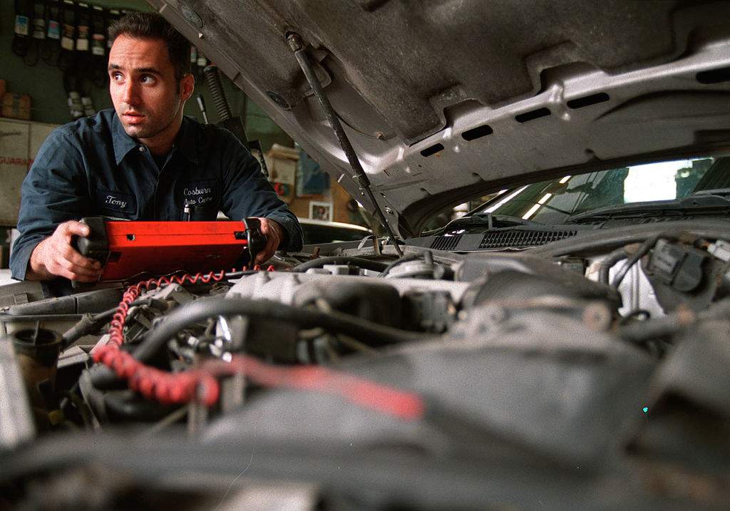 A man looks under the hood of a car