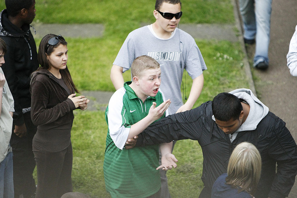 A male teenager wears an angry expression while being held back by a fellow teen