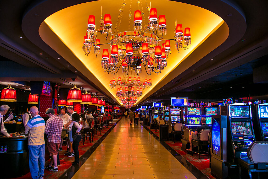 Read chandeliers line a casino hallway that separates slot machines from table games