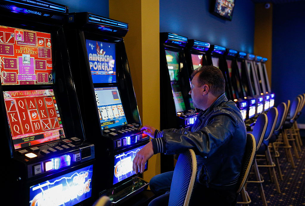 A man sits alone in a row of slot machines