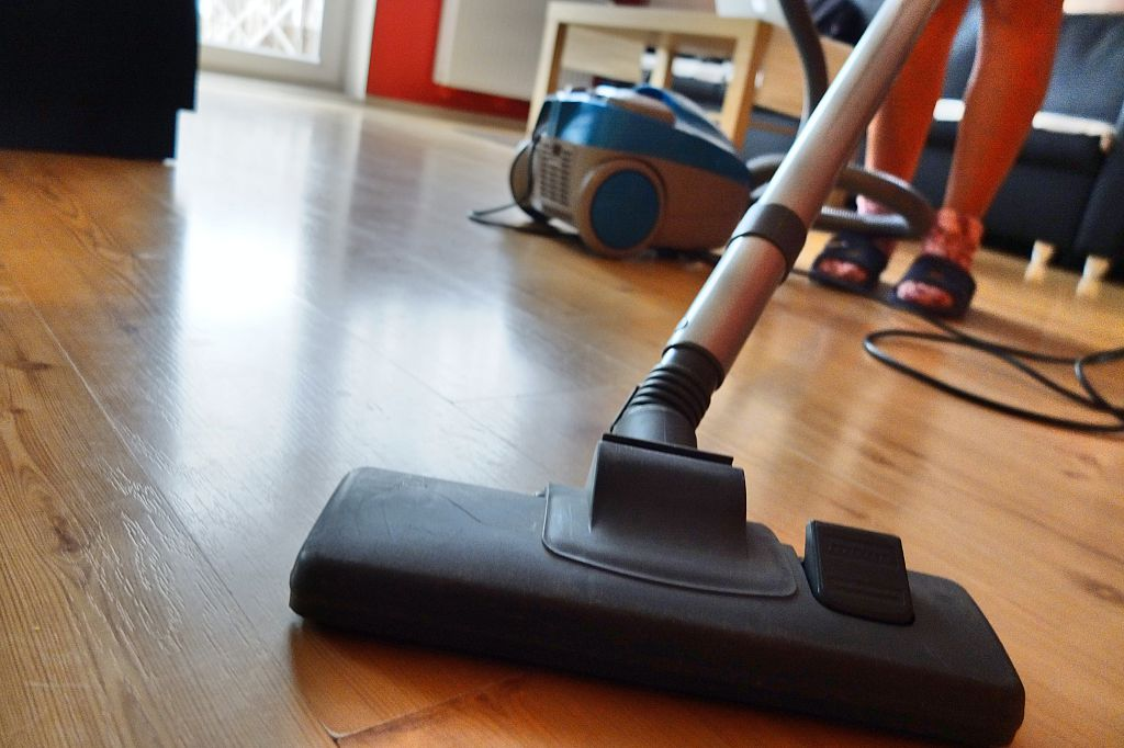 A woman vaccums hardwood floors