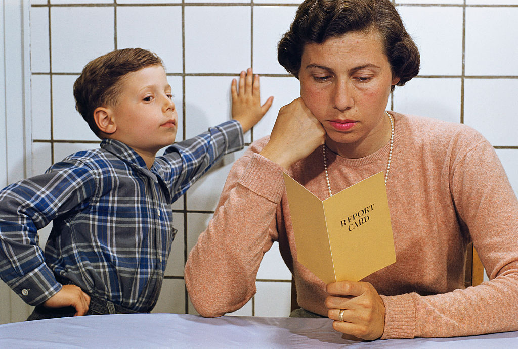 A boy leans on the wall with a hand on his hip while his disappointed-looking mother reads his report card