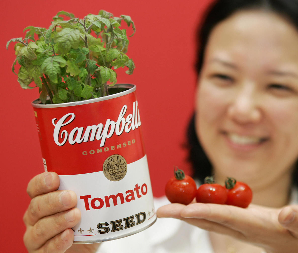 A Japanese woman displays a canned plant shaped like a Campbell's soup can,
