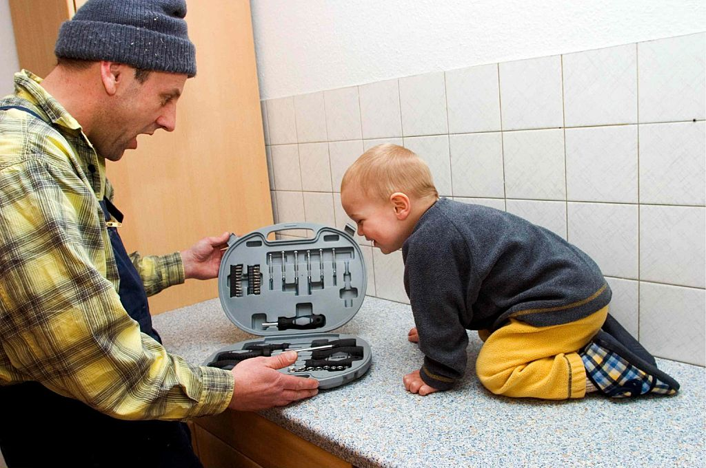 A man and toddler boy look into a tool set