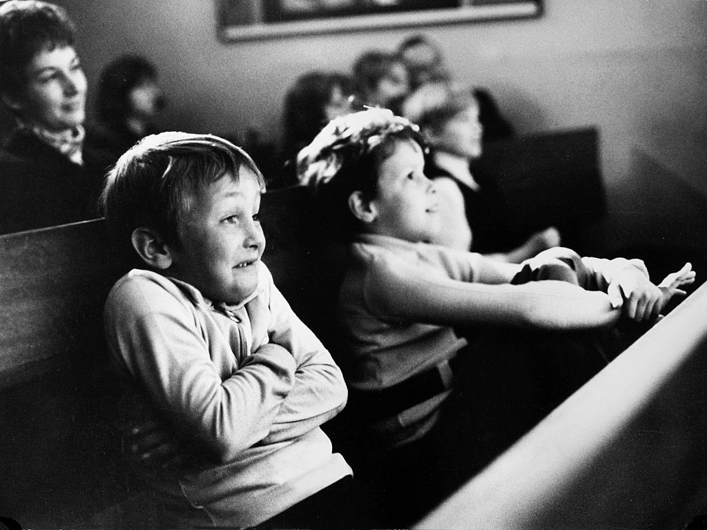 Two young boys wear amused expressions while sitting in an audience and watching a show