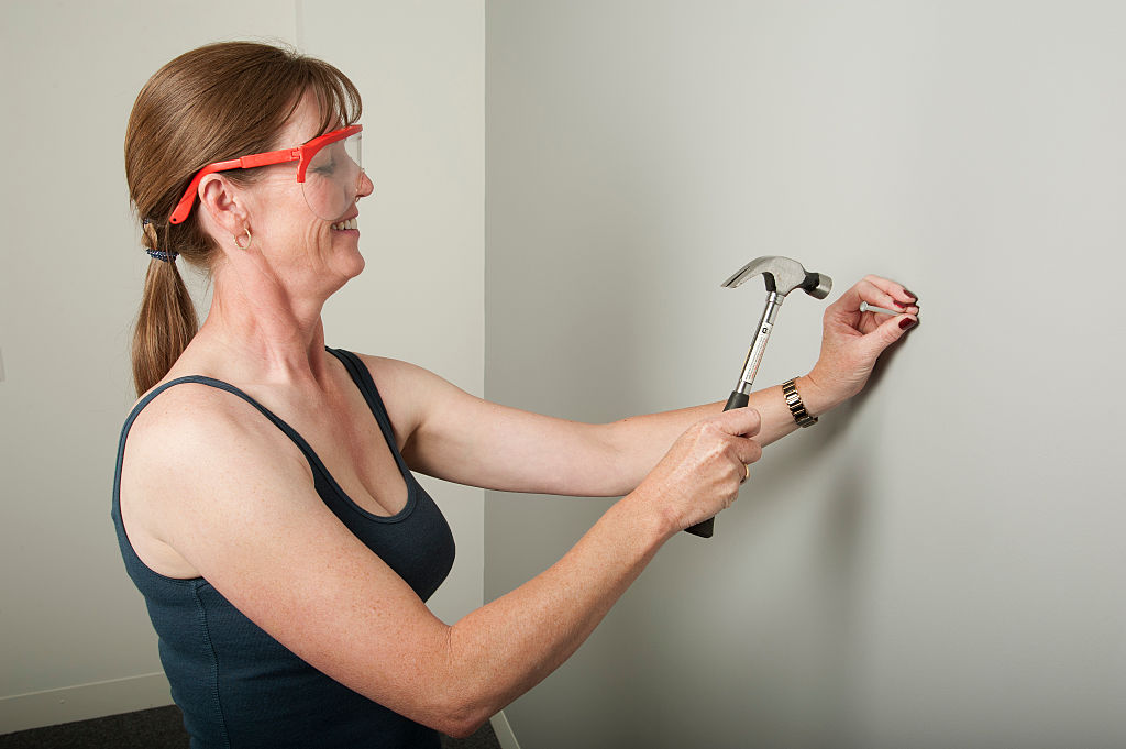 A woman hammers a nail into the wall