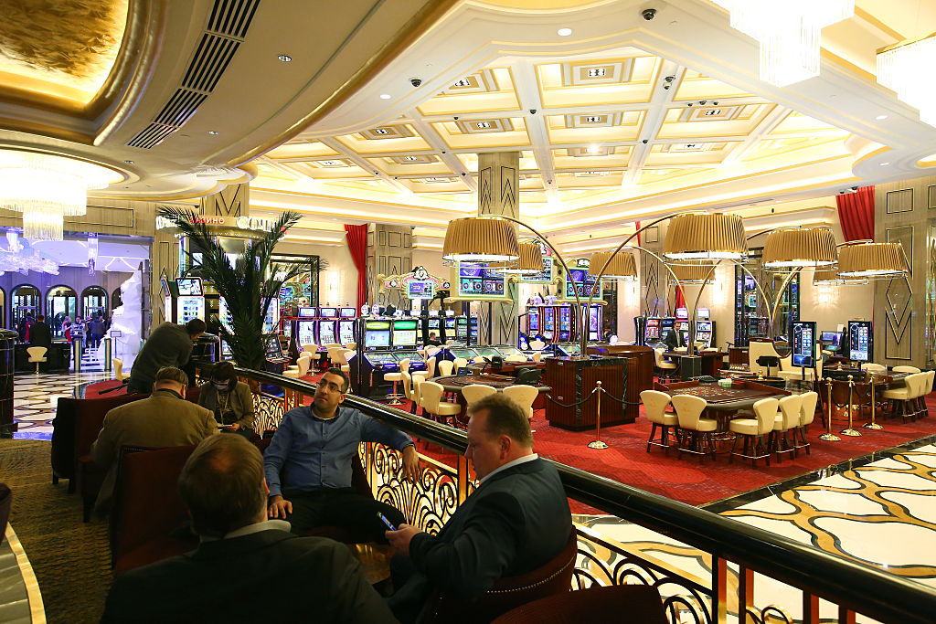 Men sit at a bar overlooking an open concept gambling area in a casino