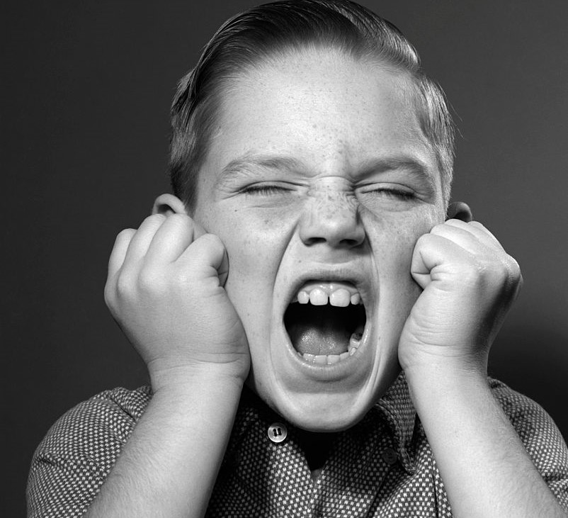 A closeup shot of a boy screaming with closed fists on either cheek