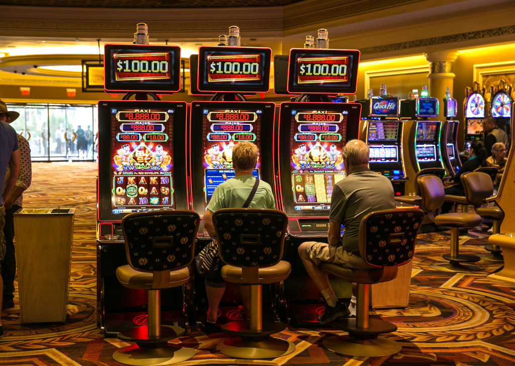 An older woman sits at a slot machine beside and older man at another slot machine in a casino