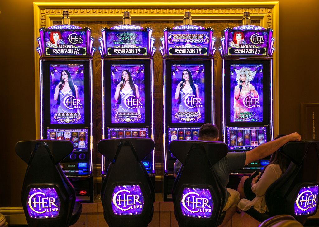 A man and woman sit before four slot machines that show singer Cher on the screen