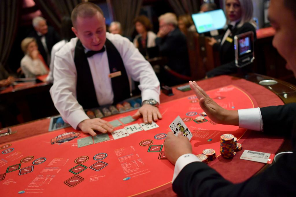 A player inticates to the dealer that he'll stay with a raised hand while holding a Jack and Five in the other hand