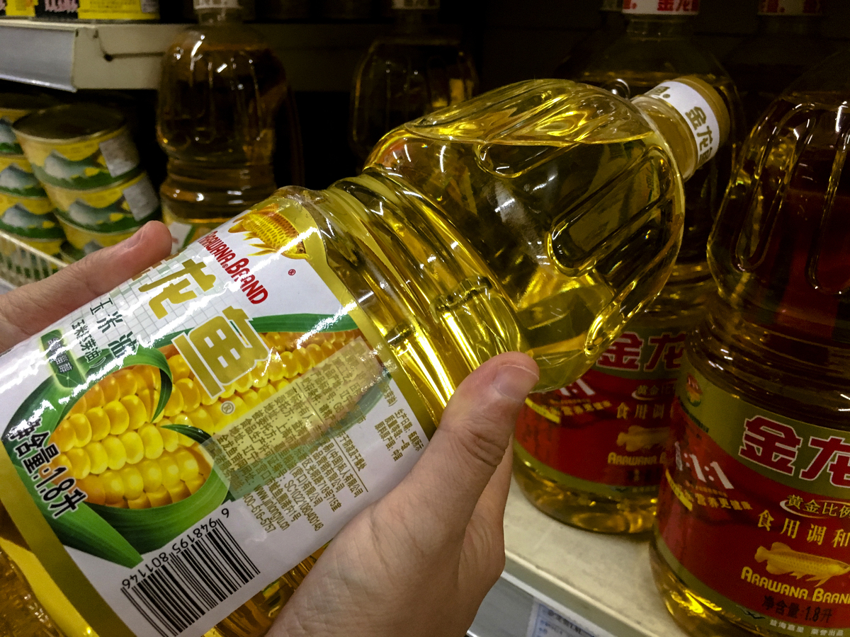 A customer is choosing a corn oil product of Arawana brand in a Chinese supermarket.
