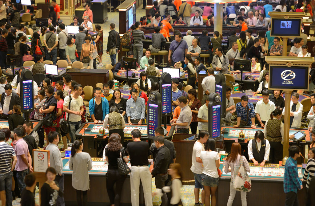 An overrun casino is packed with games tables and crowds of people