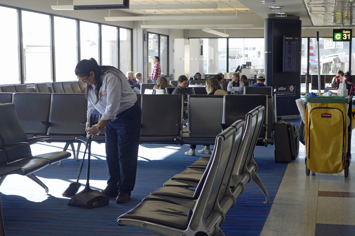 Female Cleaner Sweeping Waiting Area, Logan International Airport, Boston