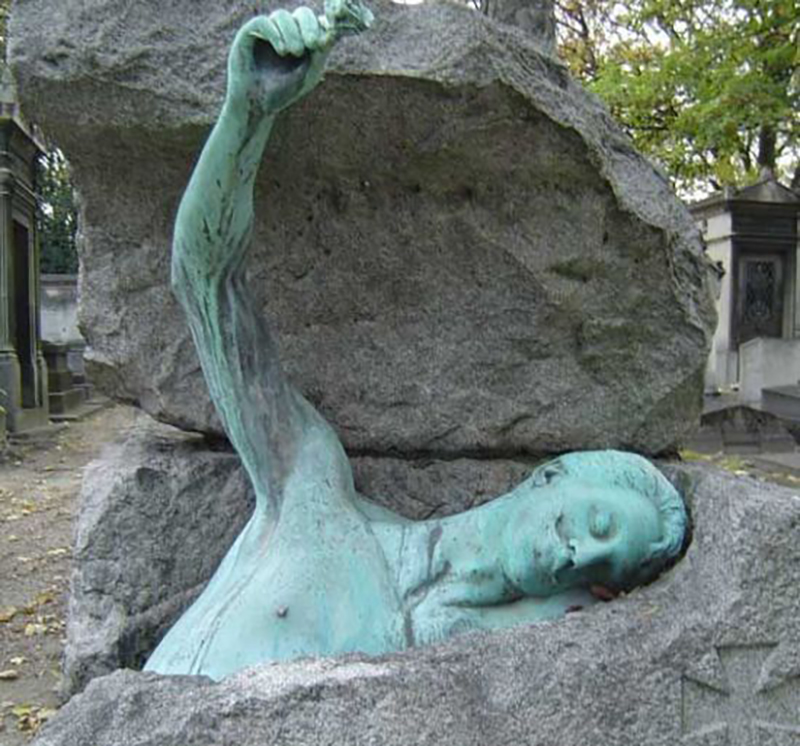 A statue appears to be pulling a rock around himself